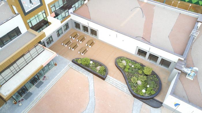 Зона відпочинку зі столиками відокремлена від площі багаторічниками / Новопечерська школа